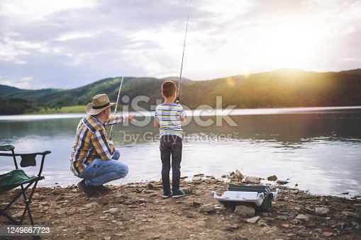 Father and son fishing at sunset in beautiful mountain lake.