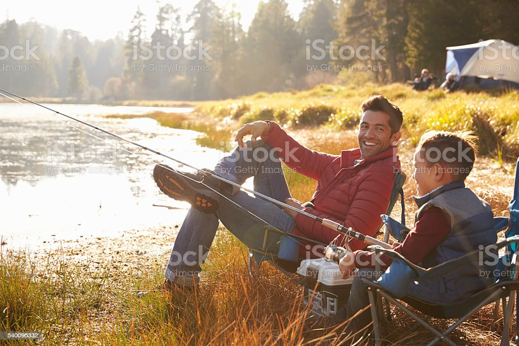 Father and son fishing by a lake, dad looks to camera stock photo