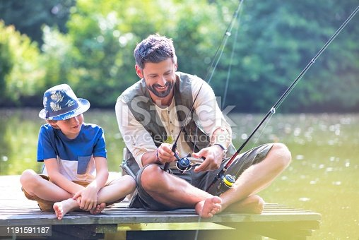 istock Father and son fishing in Lake while sitting on pier 1191591187