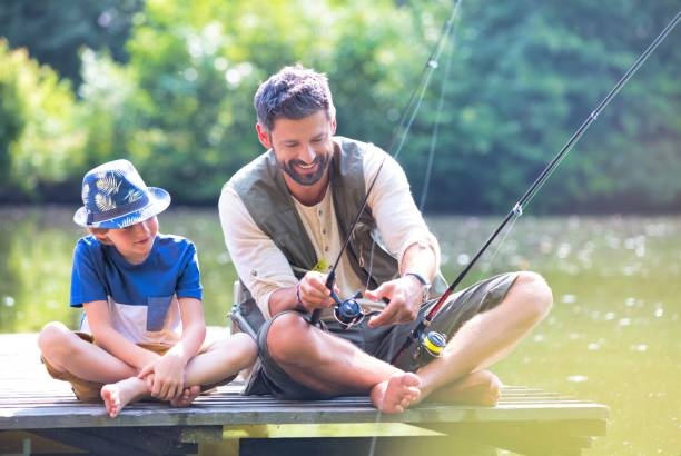 Father and son fishing in Lake while sitting on pier stock photo