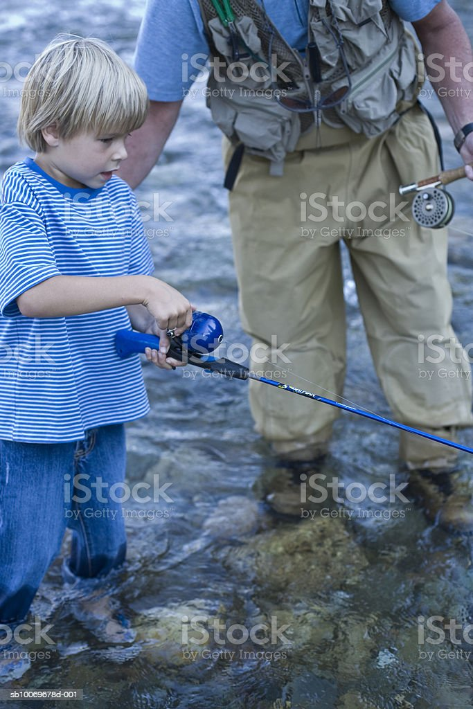 Father and son (6-7) fishing in river foto de stock libre de derechos