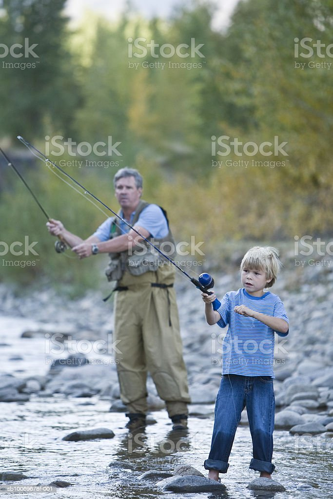 Father and son (6-7) fishing in river royalty-free 스톡 사진