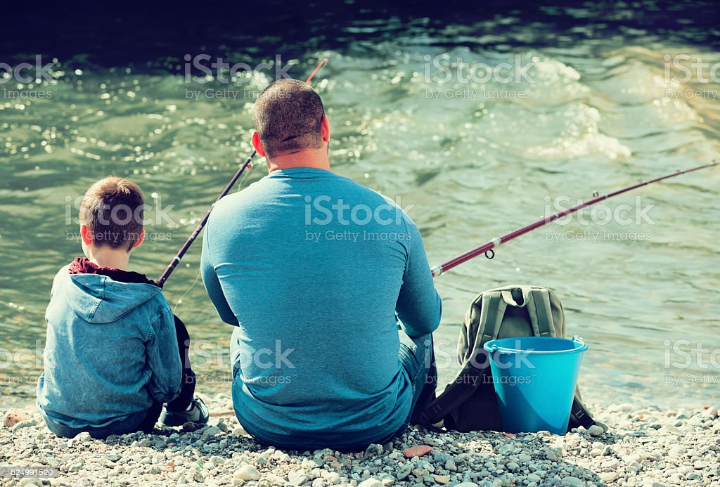 father and son fishing in wild river stock photo