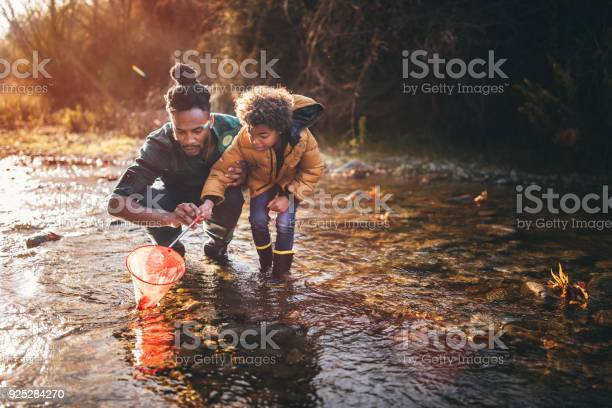 Photo of Father and son fishing with fishing net in river