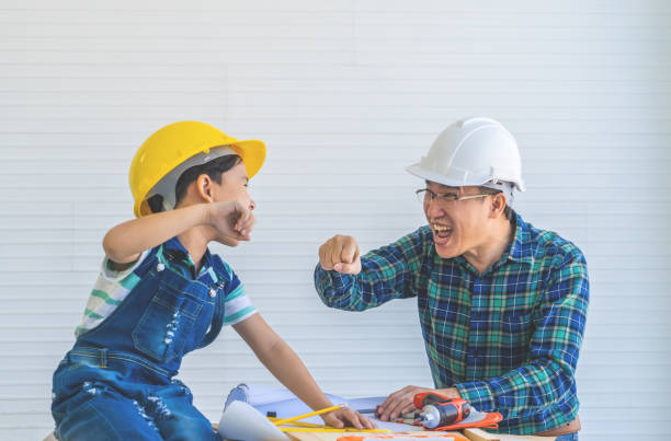 Father and Son fist bump for success concept in construction industry concept. stock photo