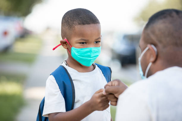 Father and son fist bump outside of school building on first day of kindergarten, while child wears mask stock photo
