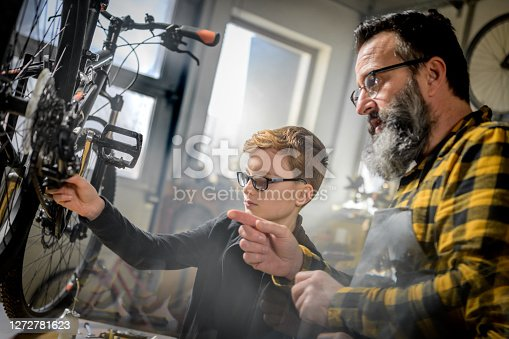 Father teaching his son how to service a bicycle in a garage workshop.
