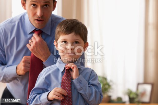 istock Father and son fixing ties together 137925657