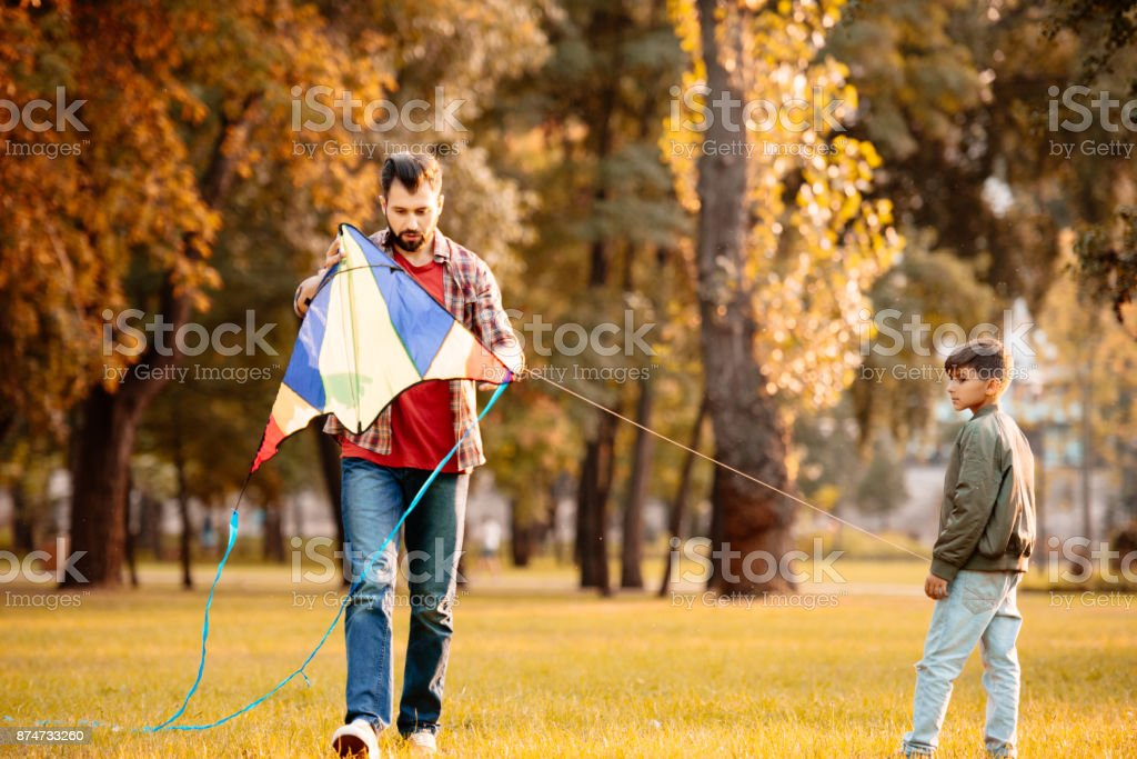 Father and son flying kite stock photo