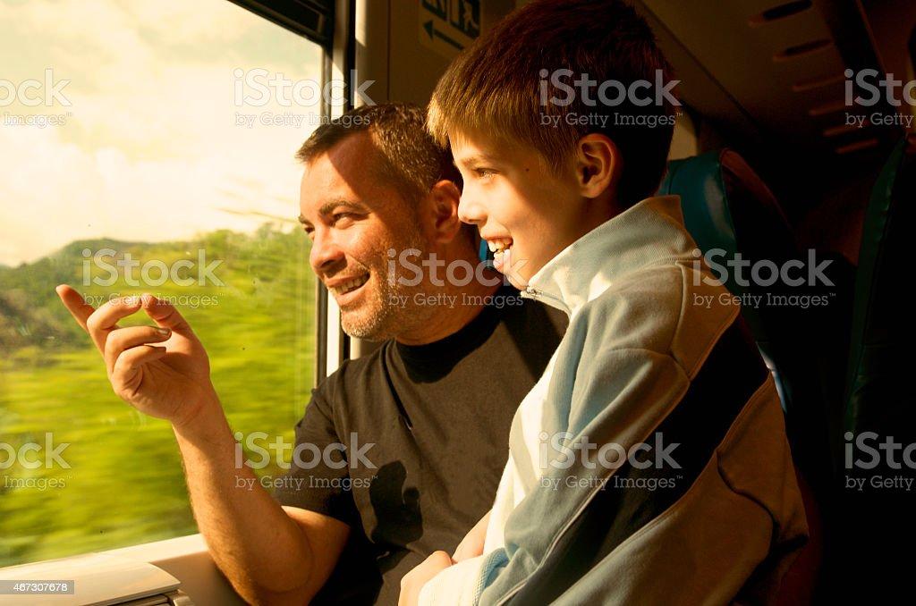 Vater und Sohn lächelnd Fenster Zug der – Foto