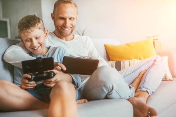 Los jugadores de juego padre e hijo se sientan juntos en casa en un cómodo sofá, usando la tableta y el gamepad - foto de stock