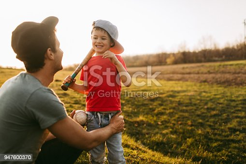 Young father and his little boy, having preparations for the baseball game