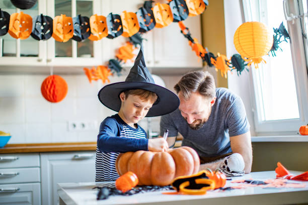 Father and son getting ready for Halloween party at home stock photo