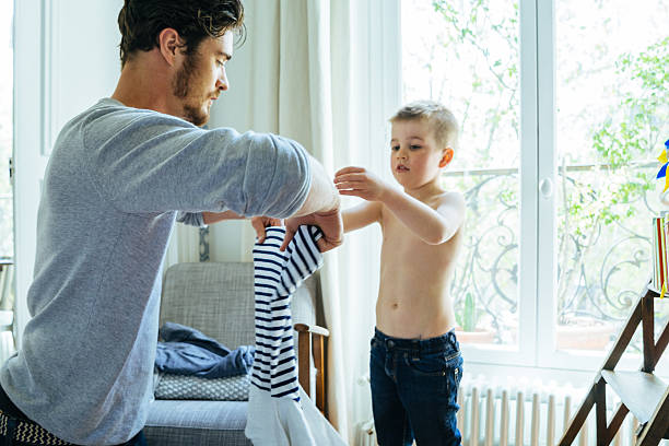 Father And Son Getting Ready In The Morning Smiling father and son getting ready in the morning. Father helping son change his clothes. fresh start morning stock pictures, royalty-free photos & images