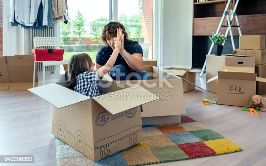 942256562istockphoto Father and son giving five after cardboard car racing 942256392