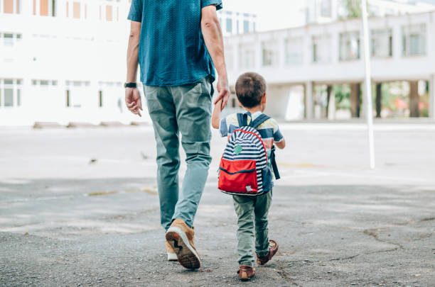 Father and son going to school. Rear view of father who leads a little boy hand in hand to the school. Father and son with backpack walking in schoolyard. genderblend stock pictures, royalty-free photos & images