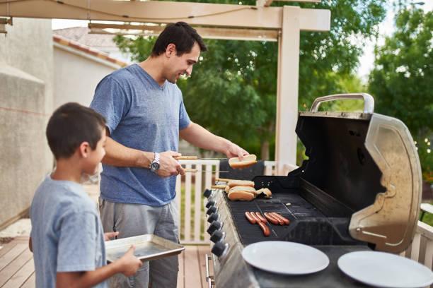 Vater und Sohn grillen Hot Dogs zusammen auf Garten Gasgrill – Foto