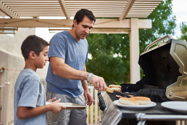 father and son grilling hot dogs together on backyard gas grill stock photo