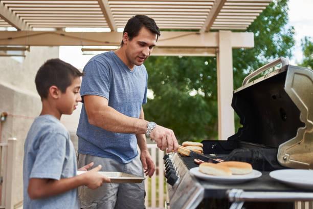 vader en zoon grillen hotdogs samen op Backyard Gas Grill foto