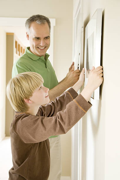 father and son hanging pictures together in home - naive malerei stock-fotos und bilder