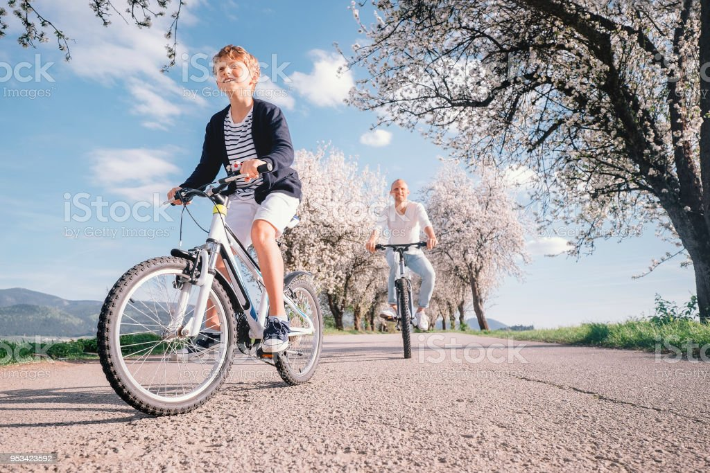 Father and son have a fun active leisure together - ride bicycles on country road stock photo
