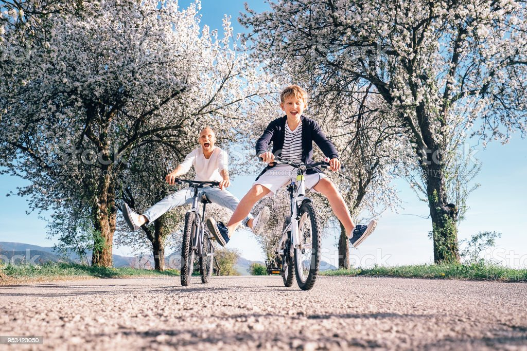 Father and son have a fun when riding bicycles on country road with blossom trees stock photo