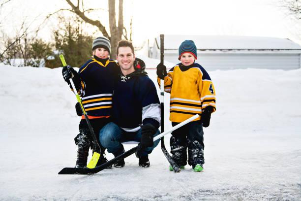 vater und sohn haben spaß hockey spielen - bruderschaft stock-fotos und bilder