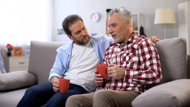 padre e hijo tomando café juntos, recordando momentos agradables, familia - happy couple sharing a cup of coffee fotografías e imágenes de stock