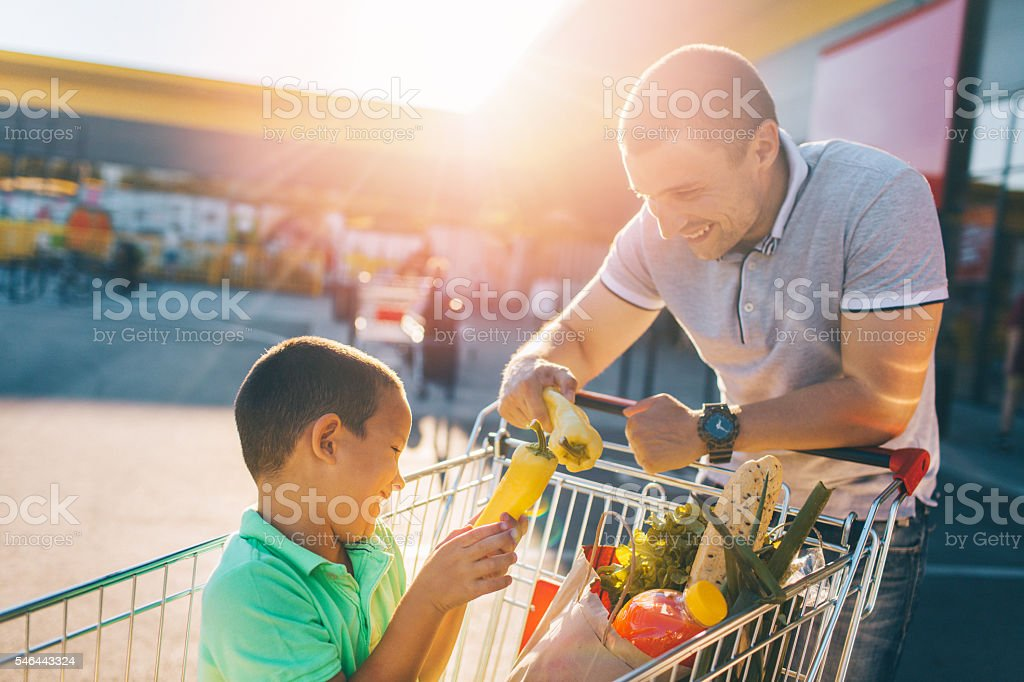 Father and son having fun after grocery shopping stock photo