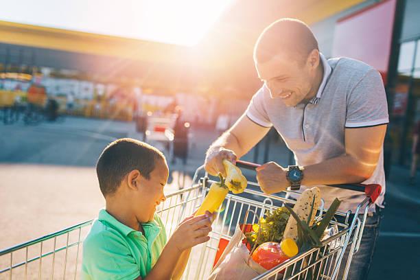 father and son having fun after grocery shopping - taschen von liebeskind stock-fotos und bilder