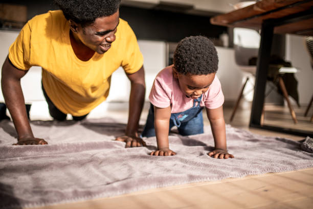 Father and son having fun doing push-ups stock photo