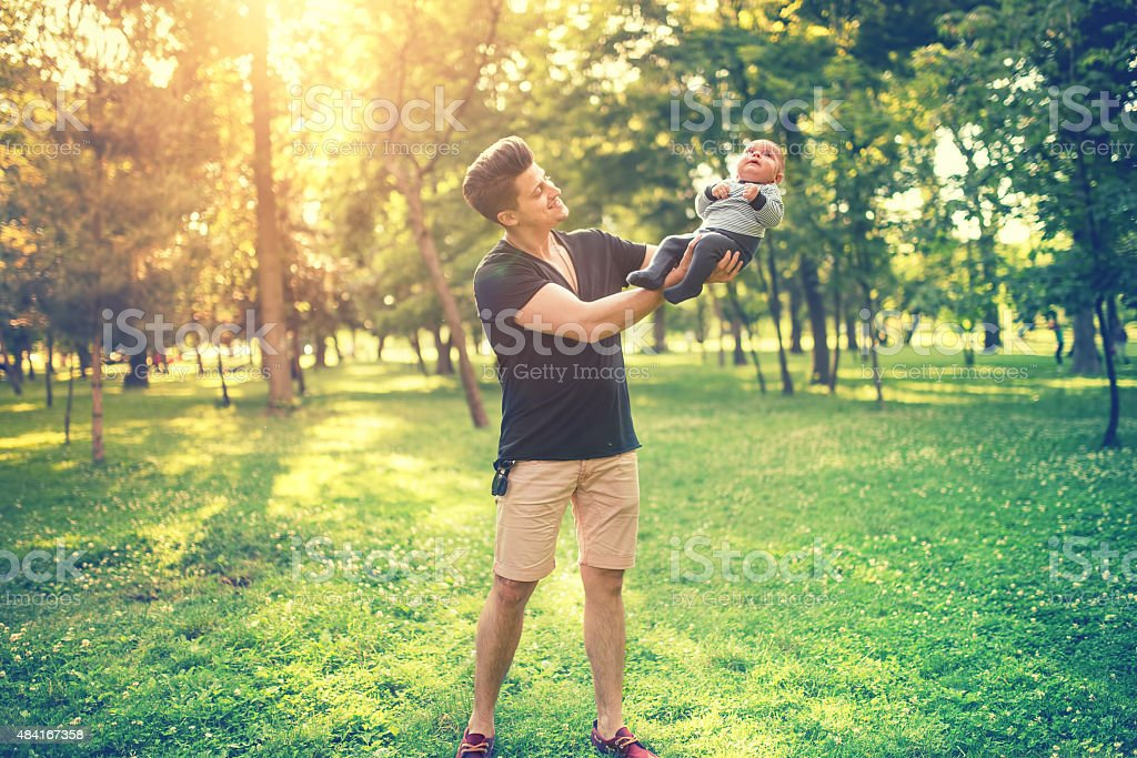 father and son having fun in park, father holding baby stock photo