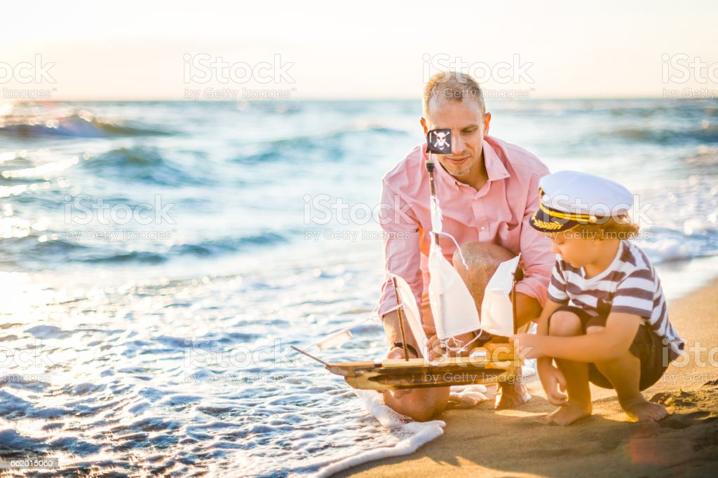 Father and son having fun on the beach royalty-free stock photo
