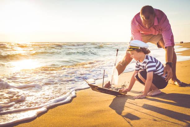 Père et fils s'amuser sur la plage - Photo