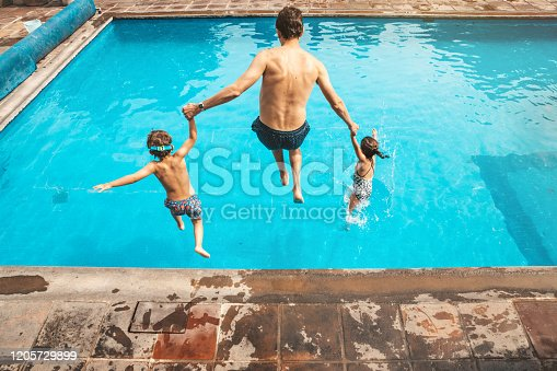 Father and son having fun on the pool