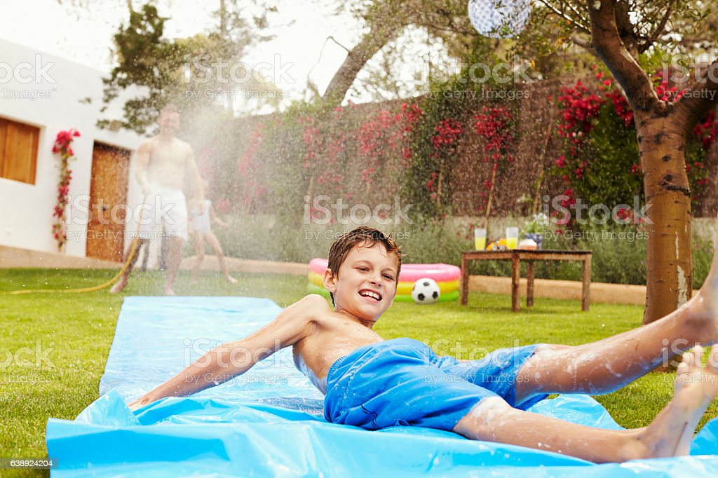 Father And Son Having Fun On Water Slide In Garden stock photo