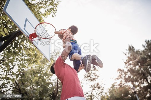 Father and son having fun, playing basketball outdoors