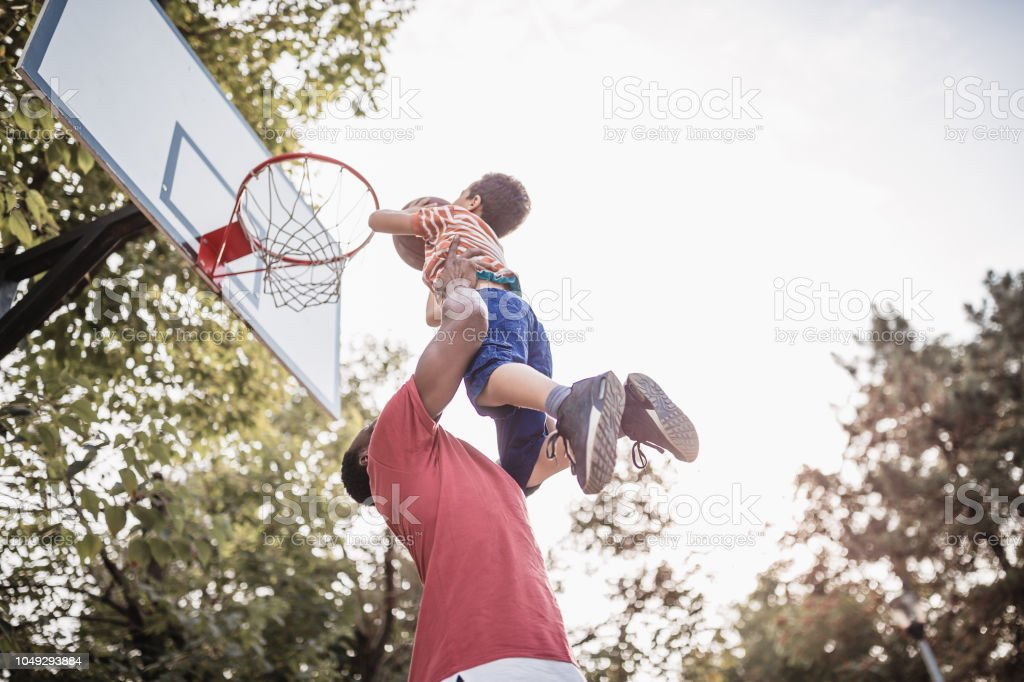 Father and son having fun, playing basketball outdoors stock photo