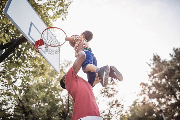 father and son having fun, playing basketball outdoors - basket foto e immagini stock