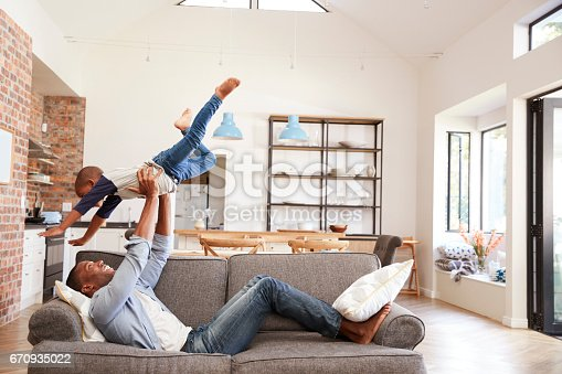 istock Father And Son Having Fun Playing On Sofa Together 670935022