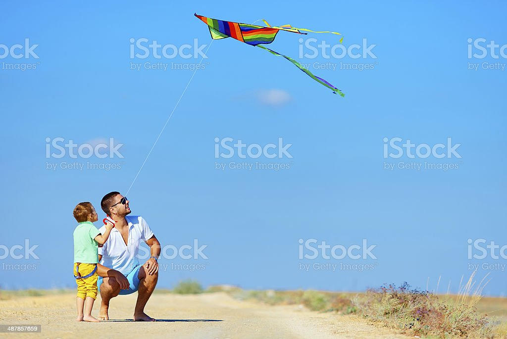 father and son having fun, playing with kite together stock photo