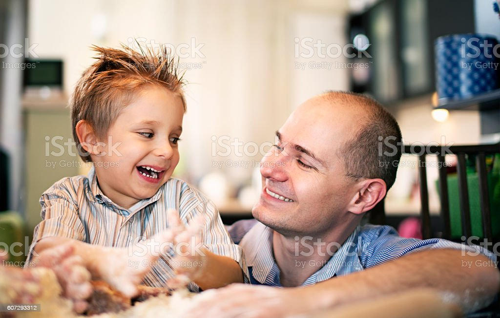 Father and son having fun with baking stock photo