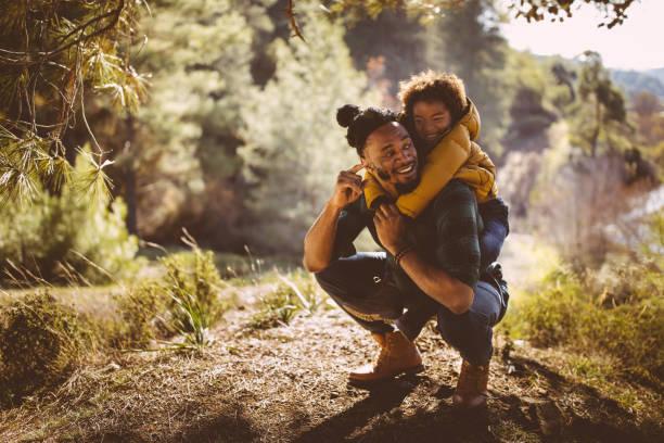 padre e hijo divertirse con piggyback ride en bosque - excursionismo fotografías e imágenes de stock
