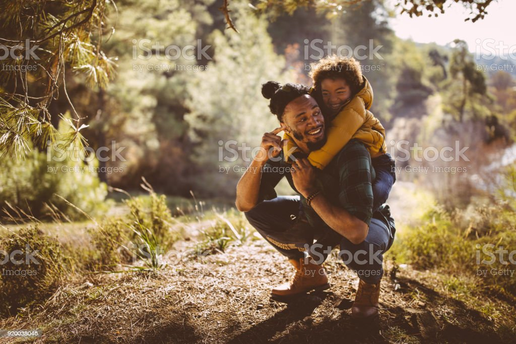 Father and son having fun with piggyback ride in forest stock photo