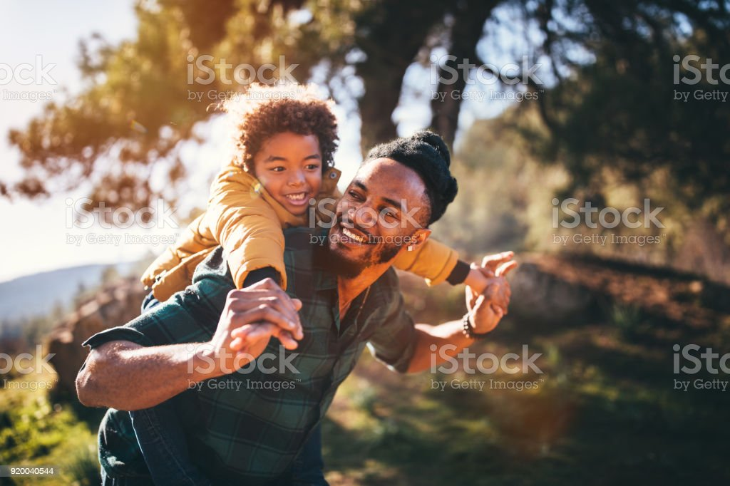 Father and son having fun with piggyback ride in nature stock photo