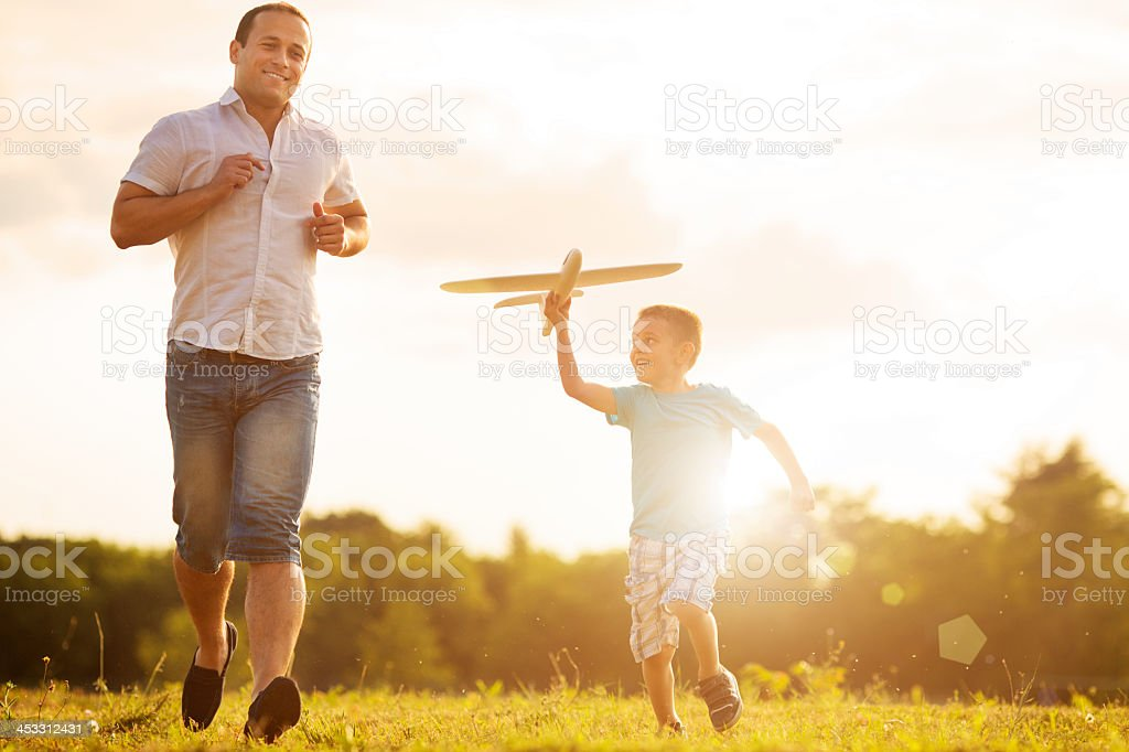 Father and son Having Fun With Toy Airplane Outdoors. stock photo