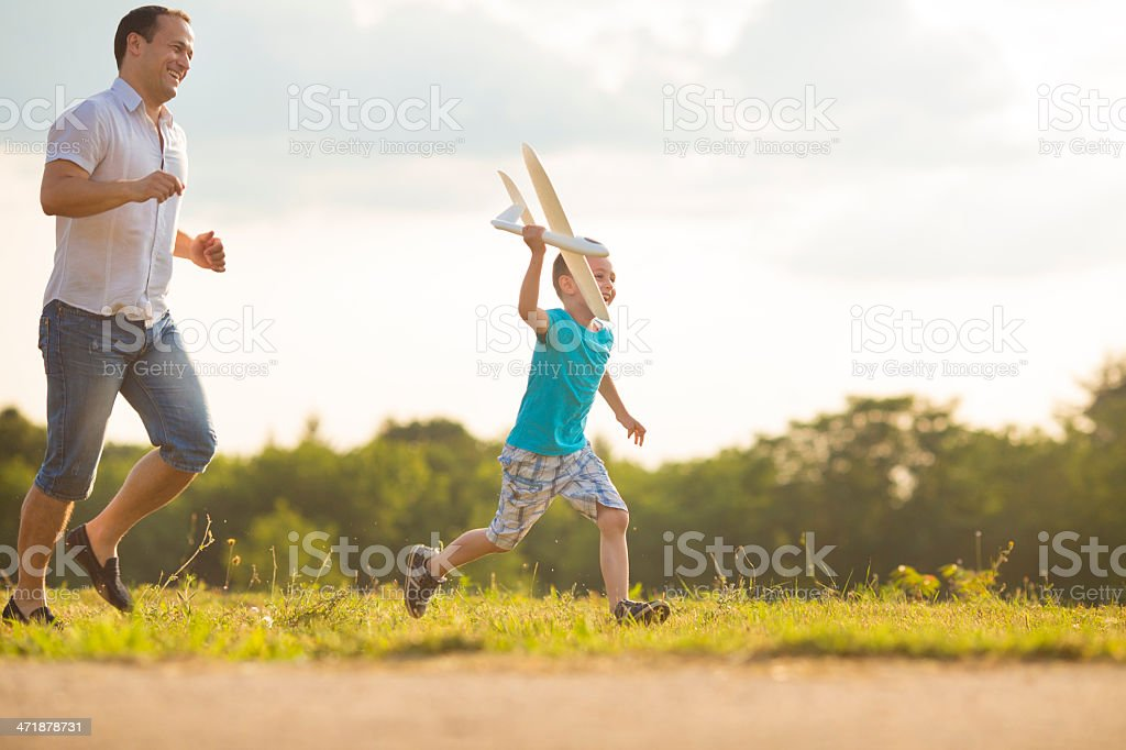 Father and son Having Fun With Toy Airplane Outdoors. royalty-free stock photo