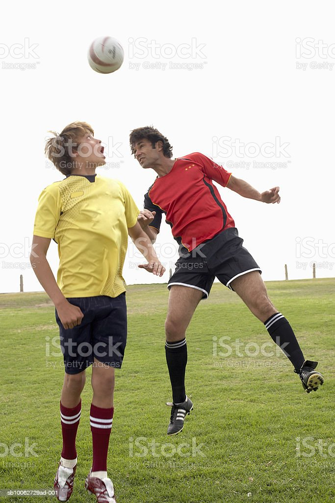Father and son (14-15) headening football foto de stock royalty-free
