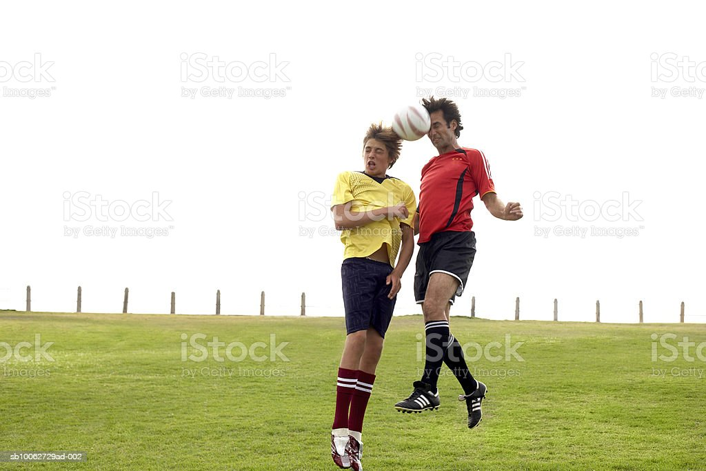 Father and son (14-15) headening football royalty-free 스톡 사진