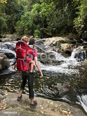 Father and son dressed in red hiking in Penedo, Rio de Janeiro, Brazil. Both standing on a rock in  looking at waterfall and river.